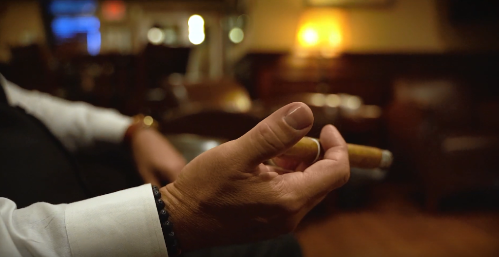 Why is it important to hold a cigar in a certain way?